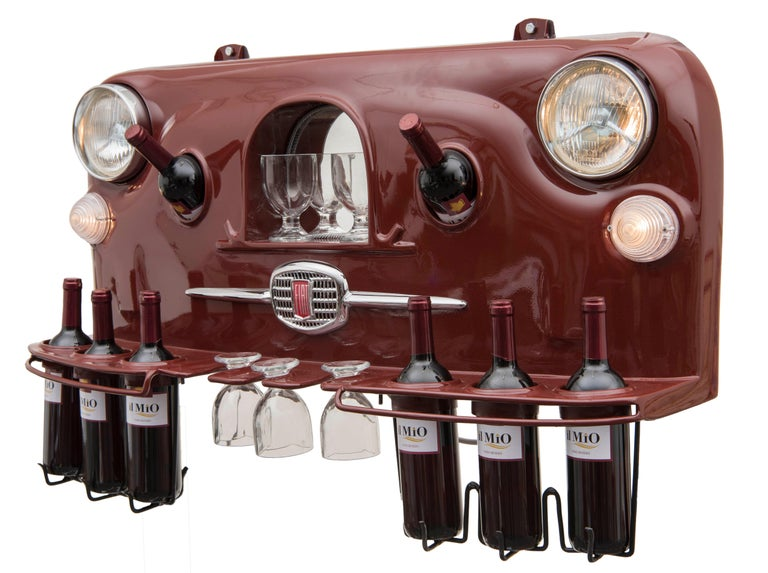 Wine holder model Rinoteca 01 is an original design artwork realized by Michele Di Gregorio in 2019.  This unique piece was realized with the anterior grille of a vintage car Fiat 500, hand-modified to contain 8 bottles of 75 cl and 5 glasses. The