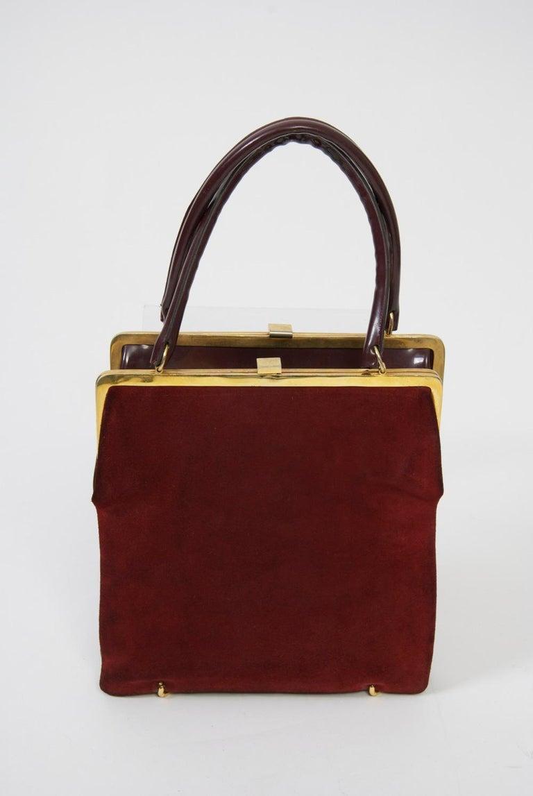Unique, innovative design, this vintage handbag, c. 1960s, consists of two identical bags connected at bottom by goldtone rings, which allow it to reverse from wine suede to wine patent. Each has an identical gold metal frame and clasp, as well as