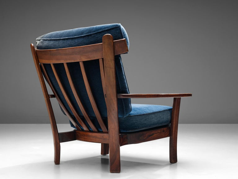 Wingback armchair, solid hardwood and velvet upholstery,Europe, 1960s.  This stately and well-executed lounge chair shows beautiful craftsmanship. The curved hard wood armrest and the velour upholstery make for a comfortable and inviting arm