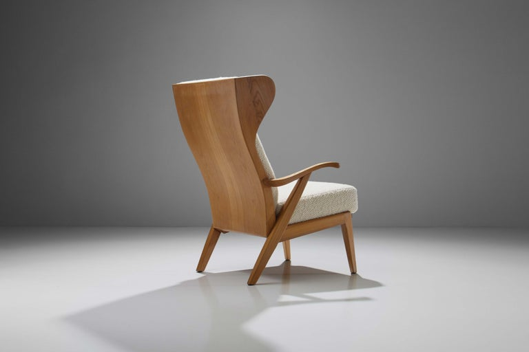"""Made by Danish Cabinetmaker Søren Willadsen in the 1960s, this elegant """"Wingback"""" chair made of elm has a distinctive shape with a high back and two wings that encompass the sitter. The armrests are gently curved inwards offering a comfortable"""