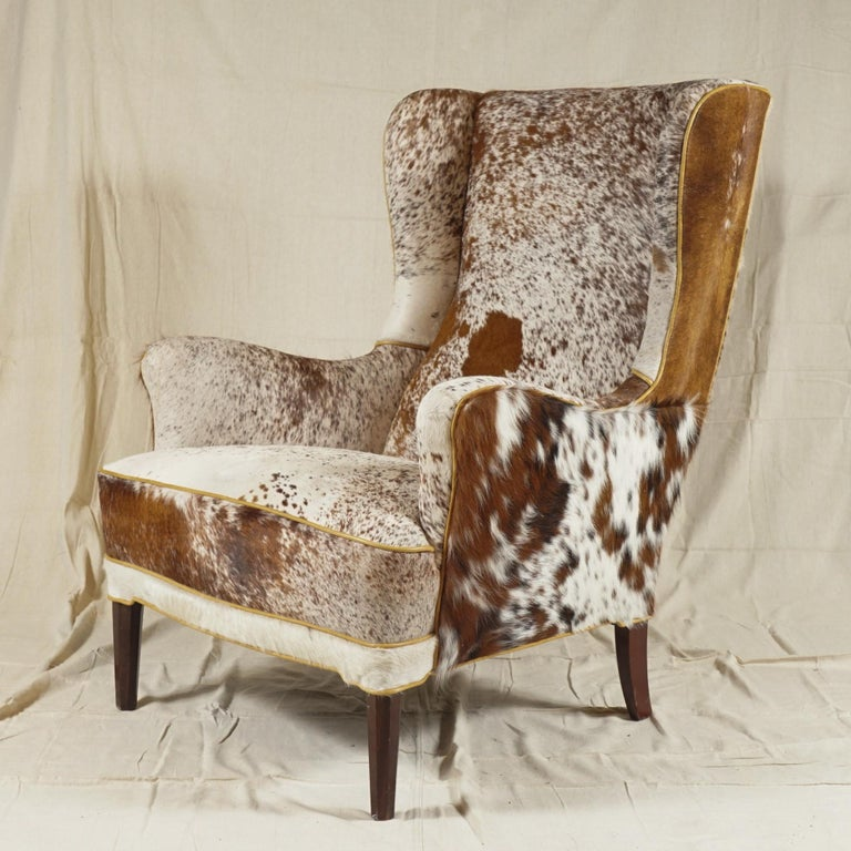 A Wingback Armchair by Danish designer Frits Henningsen, recovered in soft cowhide, extremely  comfortable. A pair available.  Frits Henningsen (1889–1965) was a Danish furniture designer and cabinet maker who achieved high standards of quality