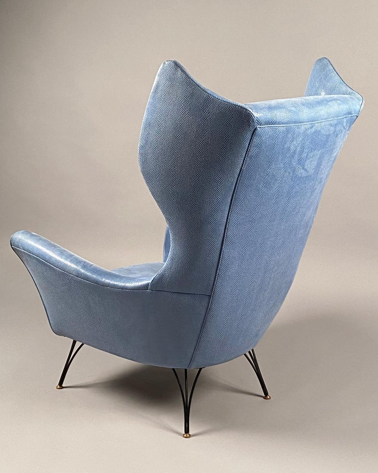 Wingback armchair of generous proportions, upholstered in a blue faux snakeskin, raised on patinated and polished bronze feet.