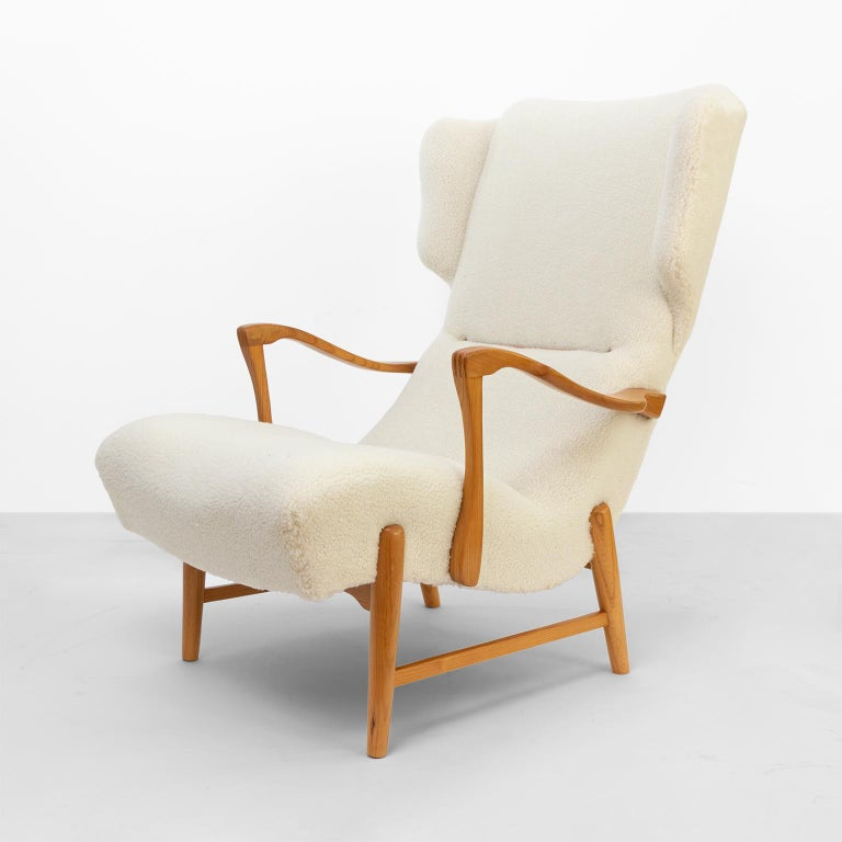 """A winged back Scandinavian Modern lounge chair with restored carved solid beechwood frame and newly upholstered in faux sheep skin fabric detailed with leather braided cords and leather buttons, from late 1940s-early 1950s. Measures: Height 39"""","""