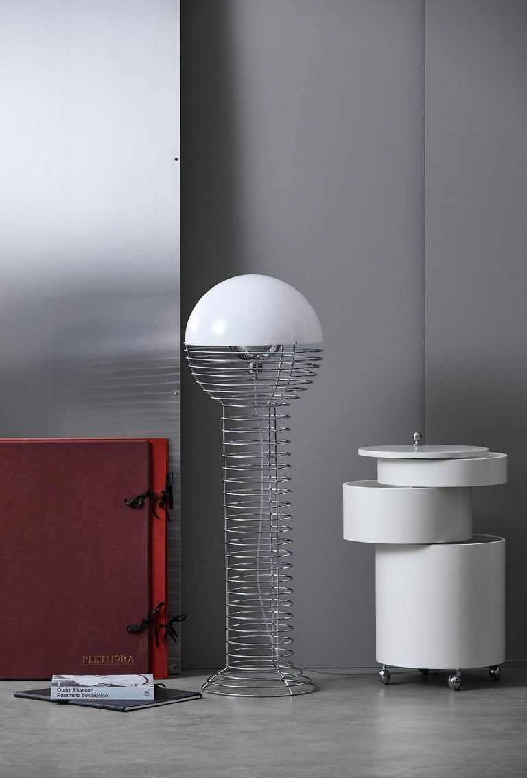 A cylindrical wire framework that widens into a hemisphere at the top. Hemispherical white plastic shade.    Material:   Frame is made of steel (chrome-plated)  Shade is made of white plastic     Light source:   E26 (110V) max. 60W    Cord: