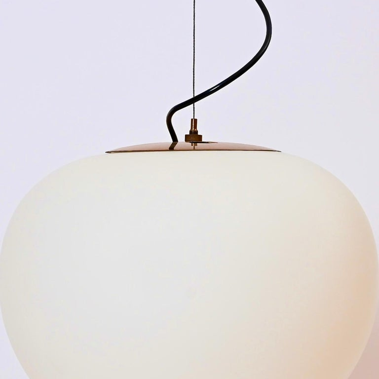 A wire-suspended opaline glass ceiling pendant designed by Bruno Gatta's innovative Milanese lighting company, Stilnovo. Produced in the 1950s, the light is suspended from a steel wire and comprises of a lacquered brass fitting and a tapered,