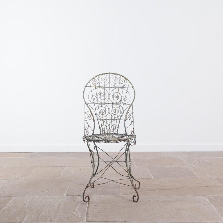 Wirework garden chair, circa 1820. The chair has been painted many times throughout its lifetime, leaving an attractive paint effect.  Measures: Height 93 cm x width 40 cm x depth 48 cm.