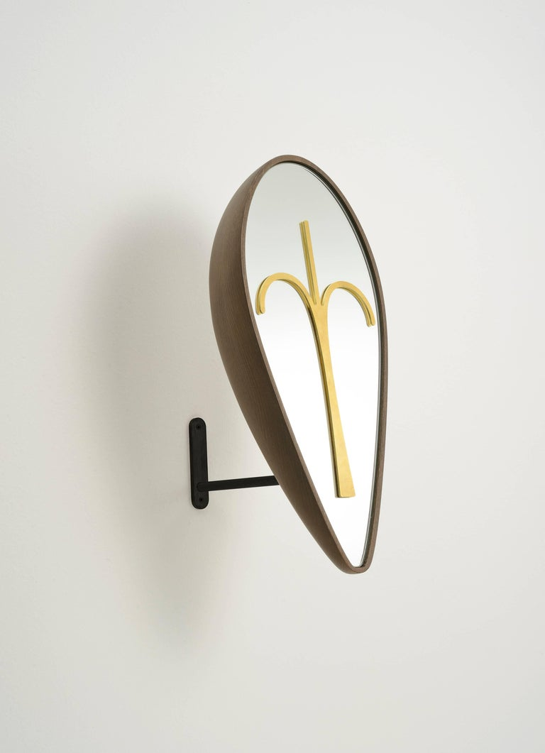 A functional mirror for a dressing room, or wooden masks and sculpture for your living or your entrance. The drop-shaped mask Bikita is made of solid beech wood stained Canaletto walnut, with a brass element on the mirror. The base is an iron stand