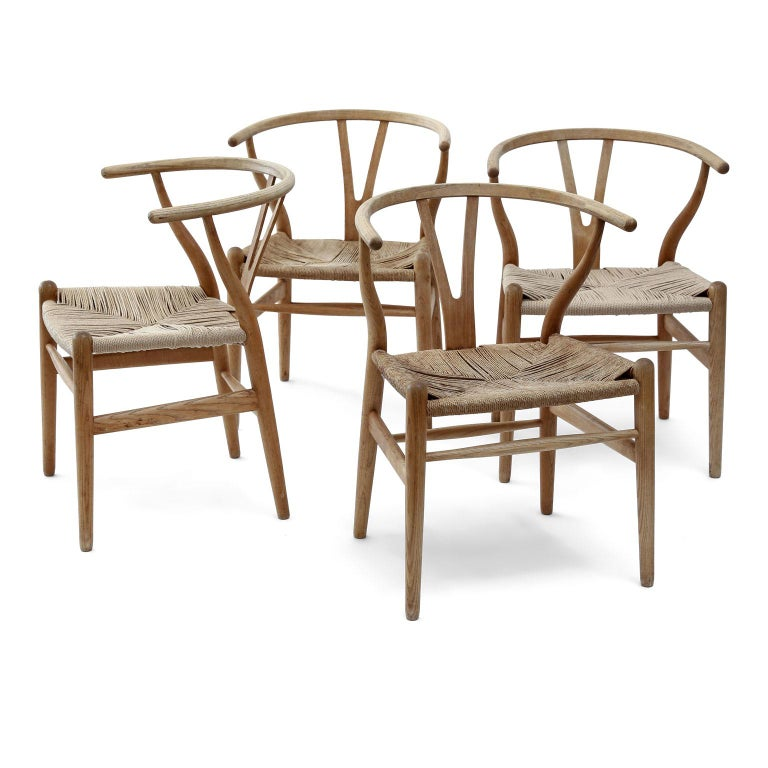 Oak wishbone armchairs by Hans Wegner (CH24) for Carl Hansen & Søn, circa 1980s. Hand carved in oak with paper-cord woven seats.