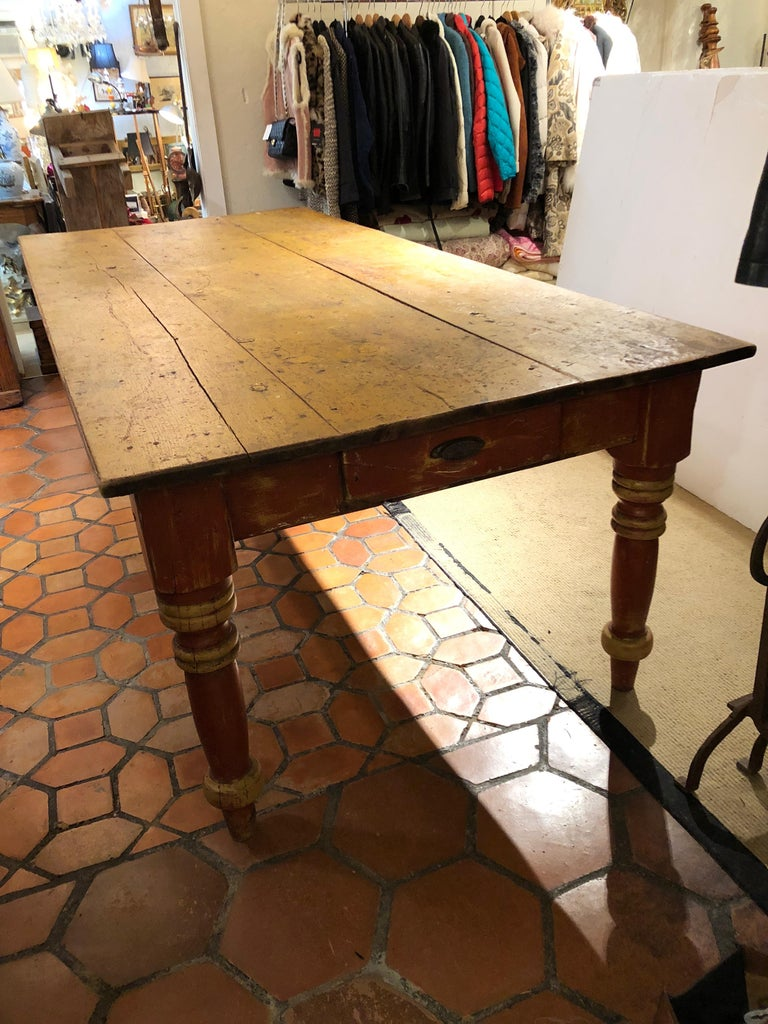 Amazing one of a kind antique Maine farm table, very large at almost 8 feet long, with gorgeous original paint and patina in warm tones of mustard, brown and red, having plank top and big turned legs as well as two drawers at each end. Apron height