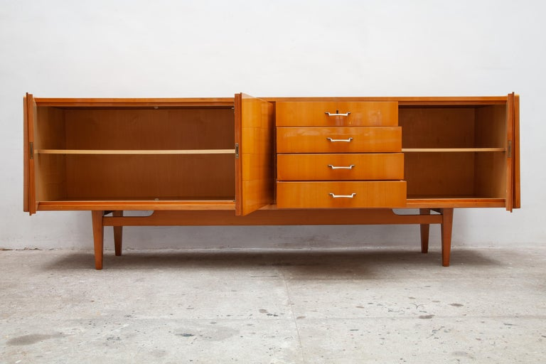 High gloss credenza made of citrus wood.  This piece is German manufacture for the Italian market.  Features two cabinet compartments with shelves and a set of 4 drawers.   The top drawer is felted for silverware and has the original key. In