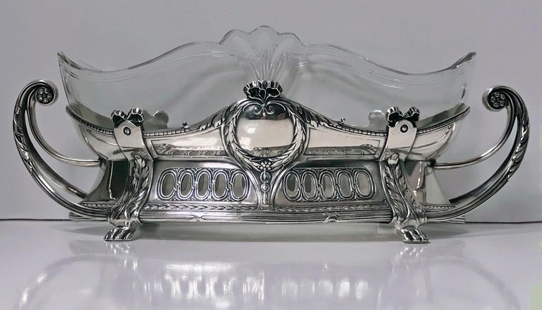 WMF centrepiece with Art Nouveau floral decoration and the original clear glass liner and silver plate. The Dish on acanthus foliate supports, curvilinear handles, the body with ovolo panel and festoon decoration. Full WMF marks to foot. Measures: