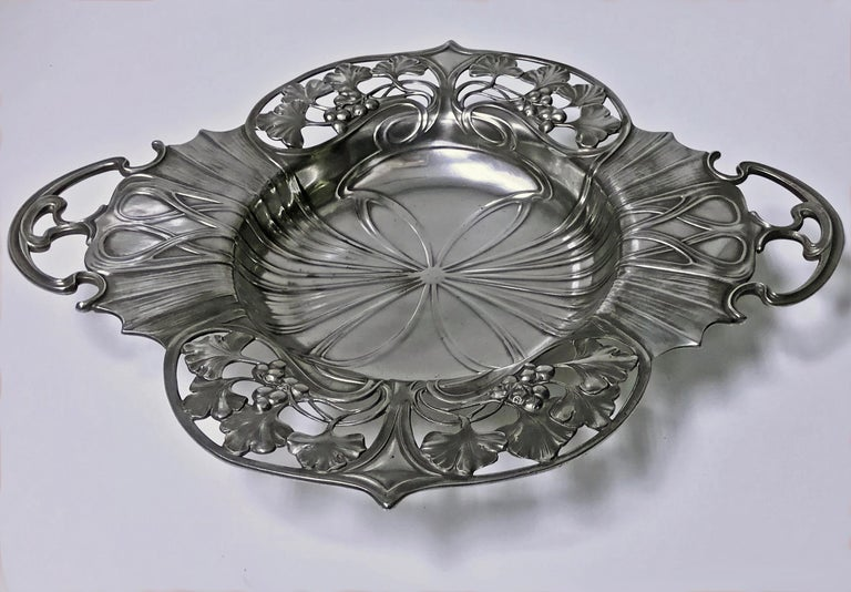 WMF Art Nouveau pewter two handled dish bowl, Germany, circa 1900. The dish on four bun feet, the shaped bowl with strong art nouveau design with pierced foliate berry sections. WMF marks to underside. Measures: 11.50 x 10.25 x 1.75 inches.