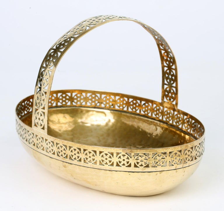 A very stylish German Jugendstil planished brass bread basket in the manner of Josef Hoffmann by WMF (Württembergische Metallwarenfabrik) and dating from circa 1910. The basket is of oval shape with a hammered body below a pierced rim with roundel