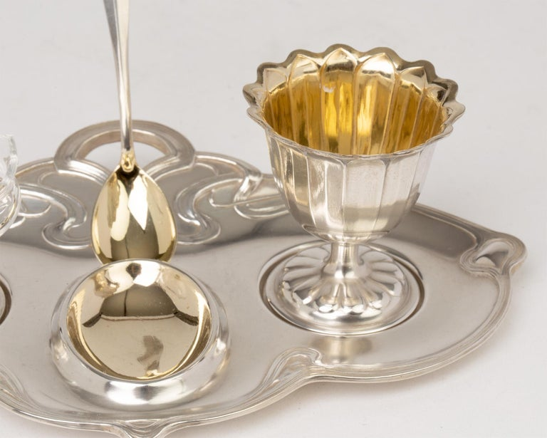 An exceptional quality WMF (Württembergische Metallwarenfabrik) German Jugendstil silver plated egg cup stand with salt and original spoon dating from circa 1900. The set comprises of a small handled tray with moulded interlaced scrolling around the
