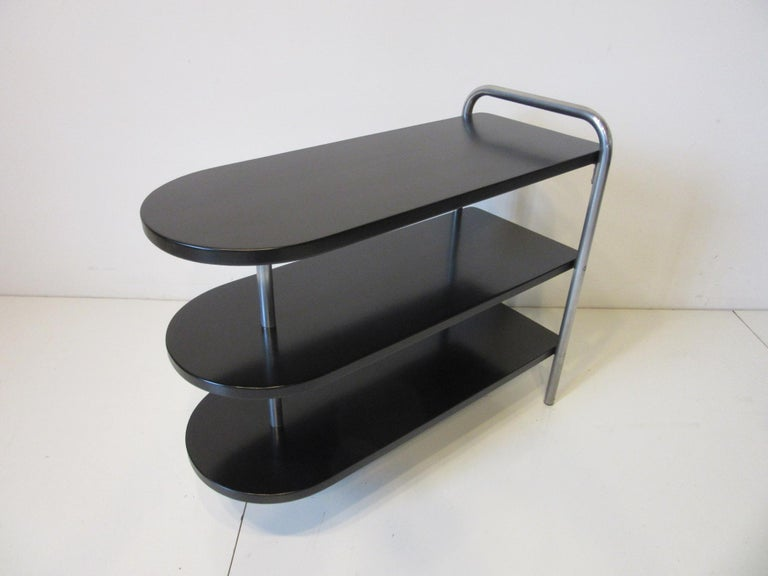 A satin black wood topped tri tiered Machine Age / Art Deco side table with chromed legs and retaining the original label to the bottom. Manufactured by the Howell Modern Metal Furniture Company.