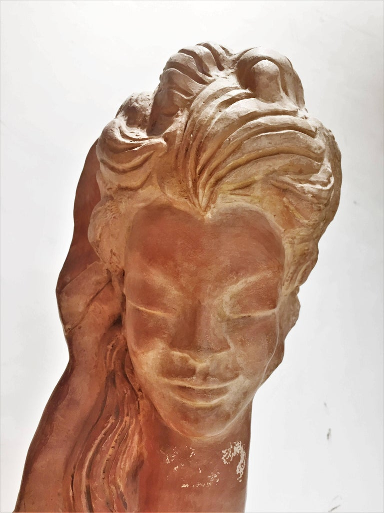 Elegant in its simplicity, this bust depicts the head of a beautiful young woman with her hair spread out over her shoulders and her eyes closed