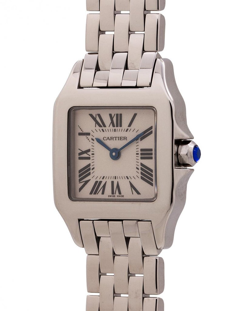 Cartier stainless steel Demoiselle, circa 2000's. 20mm case with sapphire crystal and blue sapphire cabochon crown. Classic antique white dial with Roman numerals and blue steel hands. Powered by battery quartz movement. Cartier flat link bracelet
