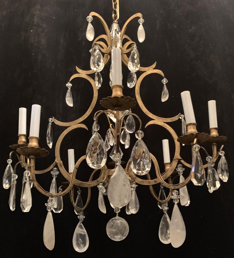 A wonderful Baguès style French rock crystal and flower crystals throughout with a gold gilt patina, over an eight-light iron bird cage form chandelier. Completely rewired and ready to install with chain and canopy.