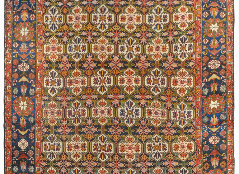 A wonderful 20th century Persian Bakhtiari rug with an all-over trellis and floral pattern woven in rich colors like crimson, gold, green, and indigo, and surrounded by a wide border containing myriad large-scale flowers and leaves, woven in the