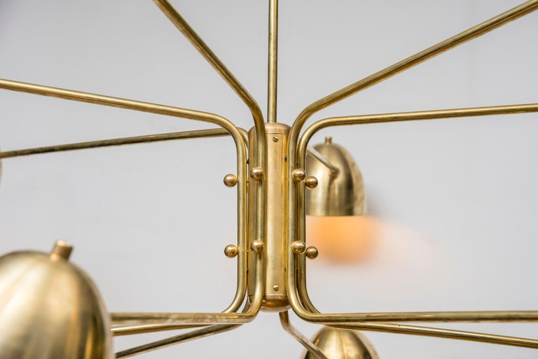This contemporary brass chandelier is composed of 12 arms, each one holding a light bulb under a brass lampshade. This is an original creation by Studio Glustin, France, 2019.