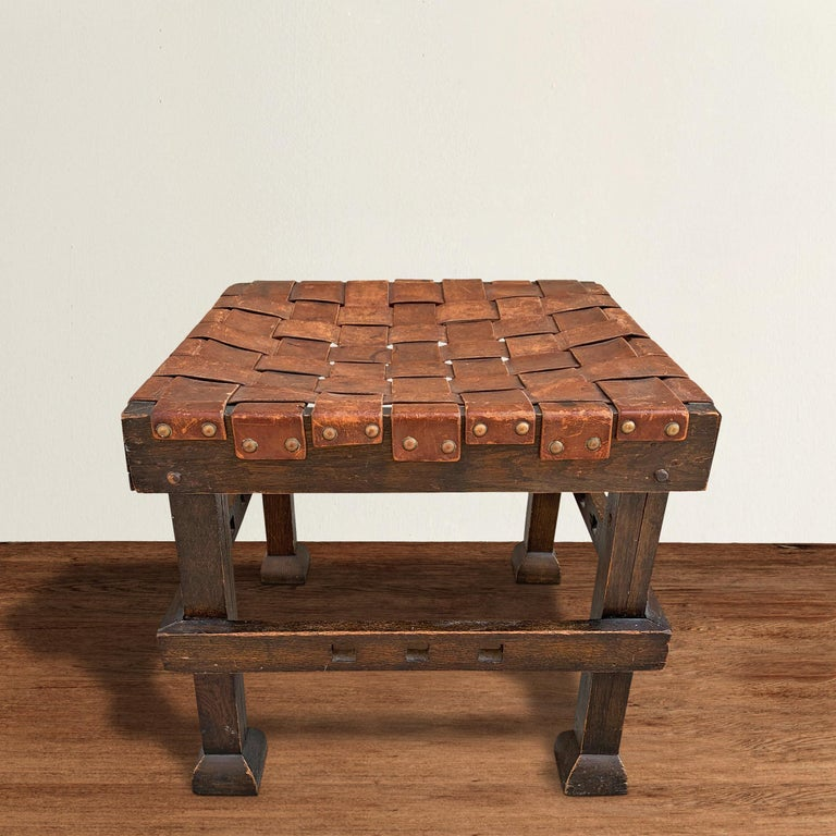 A wonderful early 20th century English Arts & Crafts period oak stool with its original woven leather top with brass nailhead trim, stretchers with a pierced square design, and fantastic flared feet. Stool also functions as a side, coffee, or