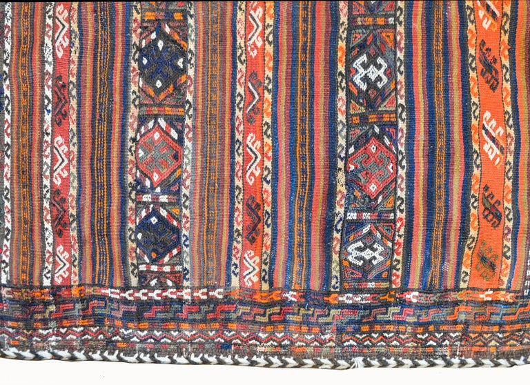 A wonderful early 20th century Persian Shahsevan bag face rug with several stylized floral patterned stripes on one side, and the reverse containing several multi-colored solid stripes all woven in indigo, coral, crimson, black, and brown.
