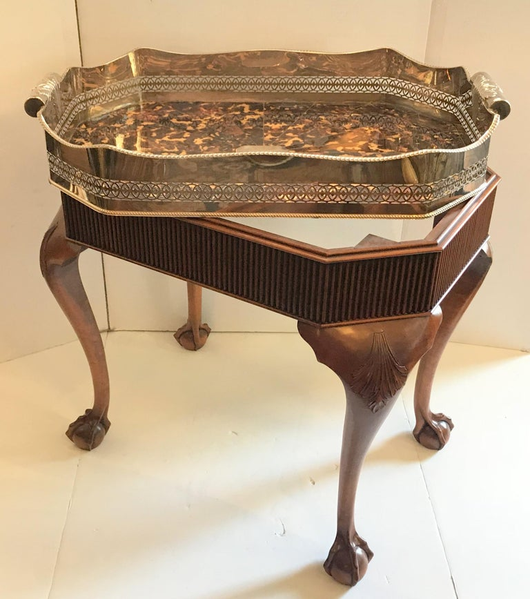 A wonderful faux tortoiseshell and silver plated English gallery tray, which can be removable from the mahogany table base that accompanies it. This beautiful serving piece has a prominent pierced and scalloped gallery and tooled with intricate fret