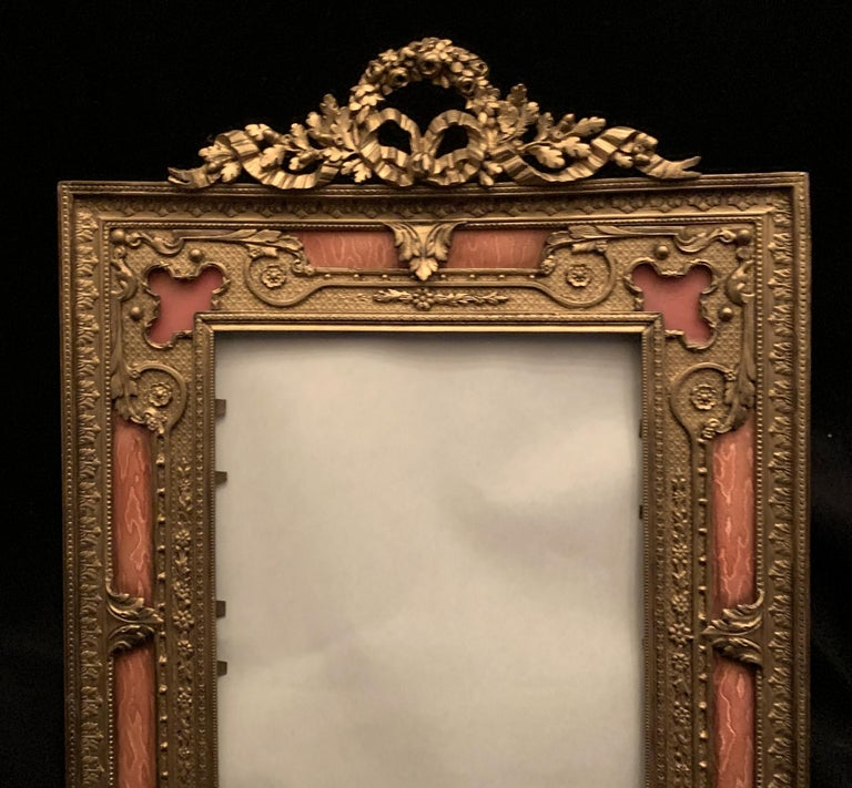 A wonderful French gilt bronze and salmon or pink enamel bow top picture frame with easel back.