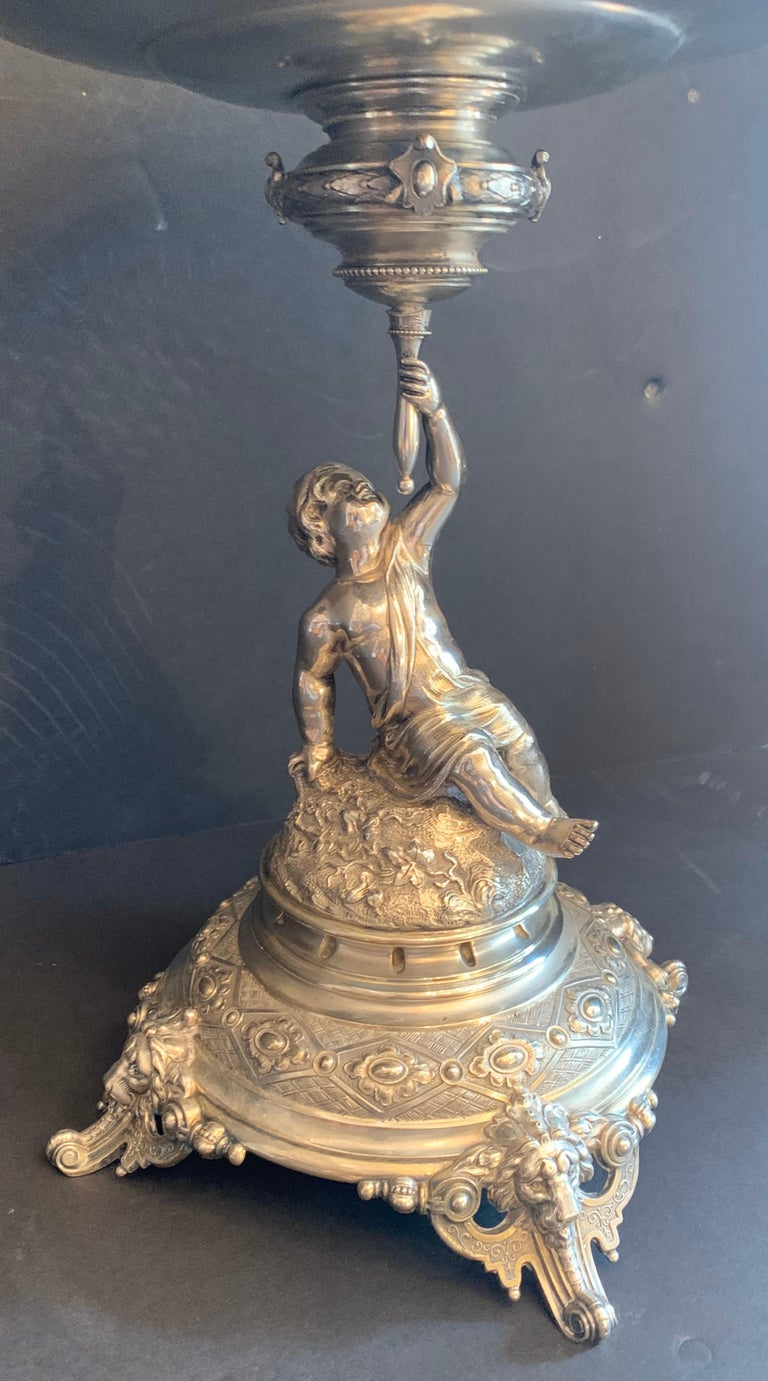 A wonderful german 800 sterling silver cherub figural centerpiece by Lazarus Posen, circa 1890 In the Rococo style, with a putti / cherub holding a filigree wreath swag and bow center bowl inset with a silver plated liner, below the cupid standing