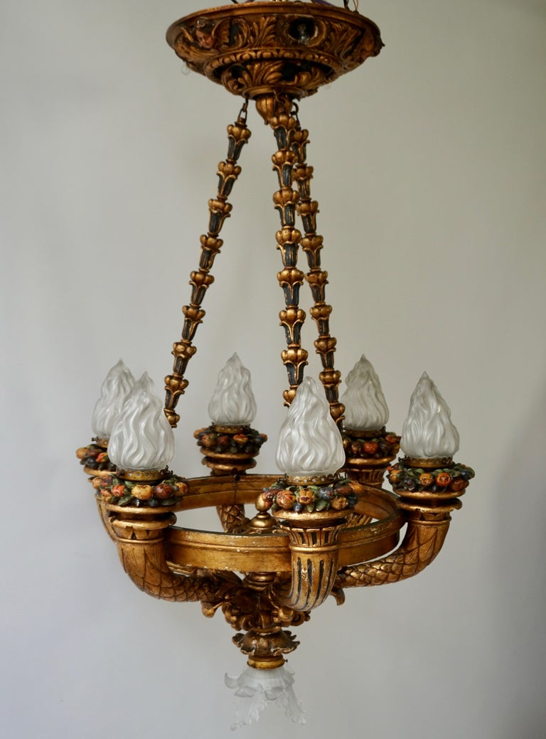 Unique Italian gilt wooden chandelier with seven lights, cherubs and painted fruit. Fine gilded wooden leaves and six beautiful angels make this rococo chandelier unique. The round giltwood ceiling plate is decorated with three painted cherubs and
