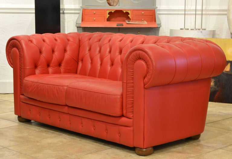 Covered with glove quality red leather and featuring excellent craftsmanship this modern Chesterfield sofa makes a very attractive impression.