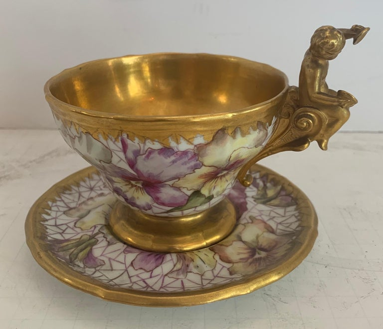 A wonderful KPM hand painted porcelain German cup and saucer set with cherub / putti and flower gold gilt decoration.