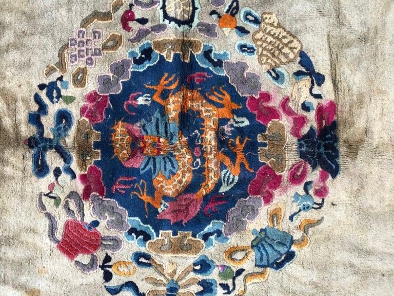 Very beautiful early 20th century large Chinese rug with beautiful design with central dragon and four dogs around, beige color field, with blue and purple. Entirely hand knotted with wool velvet on cotton foundation.