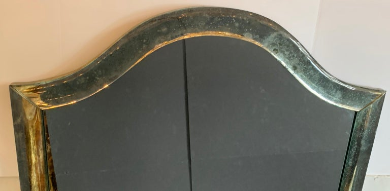 A wonderful Mid-Century Modern Venetian distressed / oxidized / pitted curved panel mirror in the manner of Karl Springer.