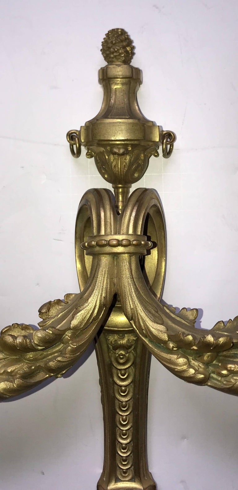 A wonderful pair of French bronze neoclassical / Regency urn top and filigree sconces in the manner of Caldwell, stamped made in France on the backs.
