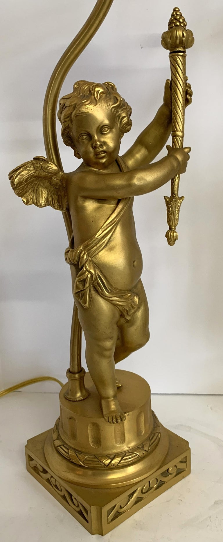A wonderful pair of French dore bronze winged cherub / putti figural sculptures holding torches converted into lamps.