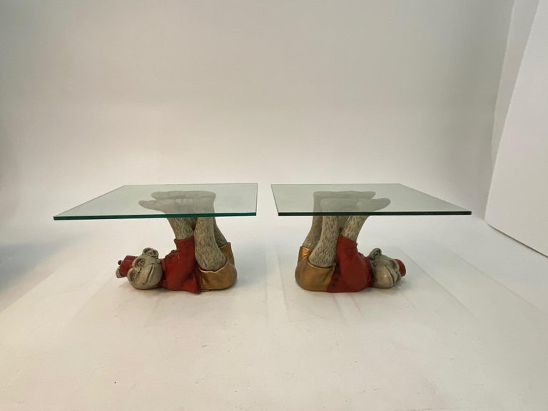 Show stoppingly fun whimsical pair of vintage monkey motife end tables having cast plaster painted apes dressed in red bellhop outfits lying in fantastic acrobatic positions on their backs, with extended arms and legs that support glass table tops.