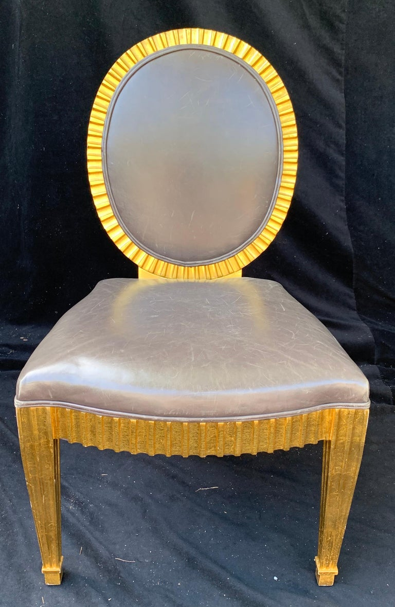A wonderful set of ten John Hutton for Donghia grey leather upholstered oval back giltwood fluted grand Soleil dining chairs. Measures: Set includes two armchairs: height of armchairs 37 3/4 inches, width 24 3/4 inches, depth 18 1/2 inches, height