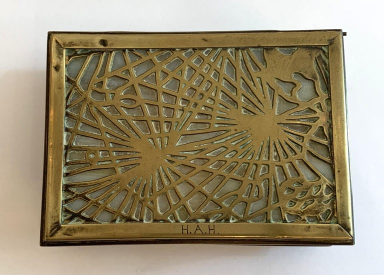 Tiffany Studios New York desk box, guaranteed authentic in the pine needle bronze pattern, with caramel or white slag glass panels on all interior sides and along the bottom. No chips one small cracks on the top corner of the glass door. Monogrammed
