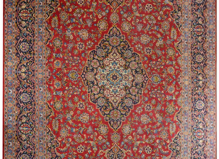 A wonderful early 20th century traditional Persian Kashan rug with a large diamond medallion amidst a field of large-scale flowers on a brilliant crimson background. The border is exceptional with multiple floral and scrolling vine patterns woven in