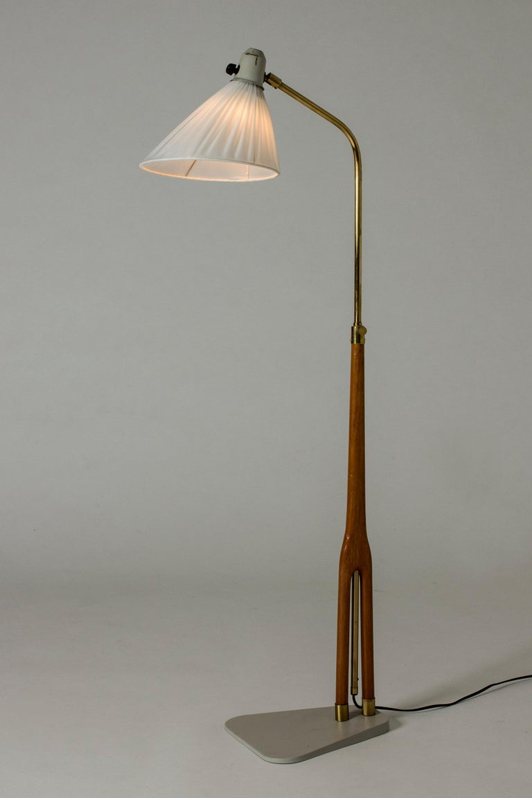 Cool floor lamp from ASEA, with a wide flat base in grey lacquered metal. Wood and brass handle. Graphic lines and nice combination of materials.