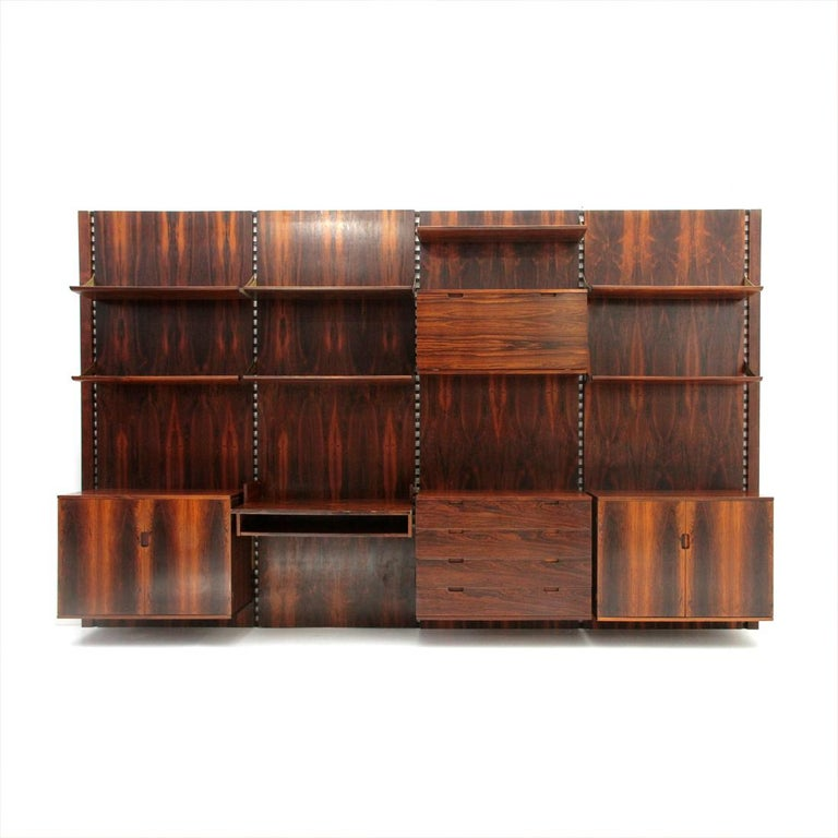 Library produced in the 1960s by Mobilia. Wall panels and elements in veneered wood. 7 tapered front edge shelves. 1 bar unit with flap and internal compartments. 2 storage compartments with doors and internal shelf. 1 chest of drawers with