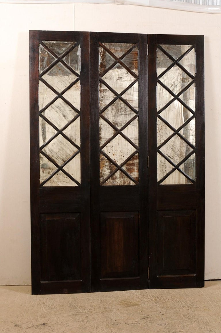 A free-standing mirrored three-panel folding screen room divider from the mid-20th century, Britain. This vintage screen features three-connected sections, each having a carved-wood raised panel at bottom, and a diamond-pattern lattice at top half