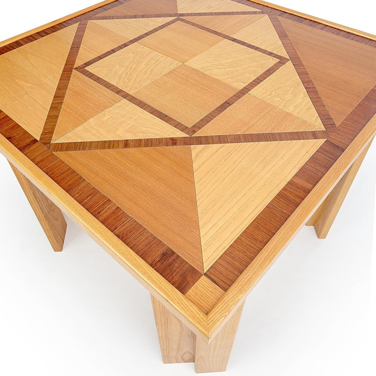 This distinctive dining table is entirely handcrafted using traditional woodworking techniques, boasting an exquisite geometric square inlay top embellished by decorative sections of oak-, rosewood-, and ash-veneered wood. A striking feature of this