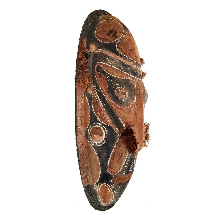 A hand carved mask from the lower Ramu River, Murik Lakes, Papua New Guinea. Late 1970s. Natural pigment and fiber decorations, framed by woven cane.