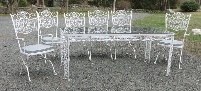 A rare Woodard Andalusian pattern patio dining set. The set is painted white with some chipping and rust. The cushions are included but one zipper is broken. The wire mesh seats are in good condition. The table is 34.75' wide, 72.5