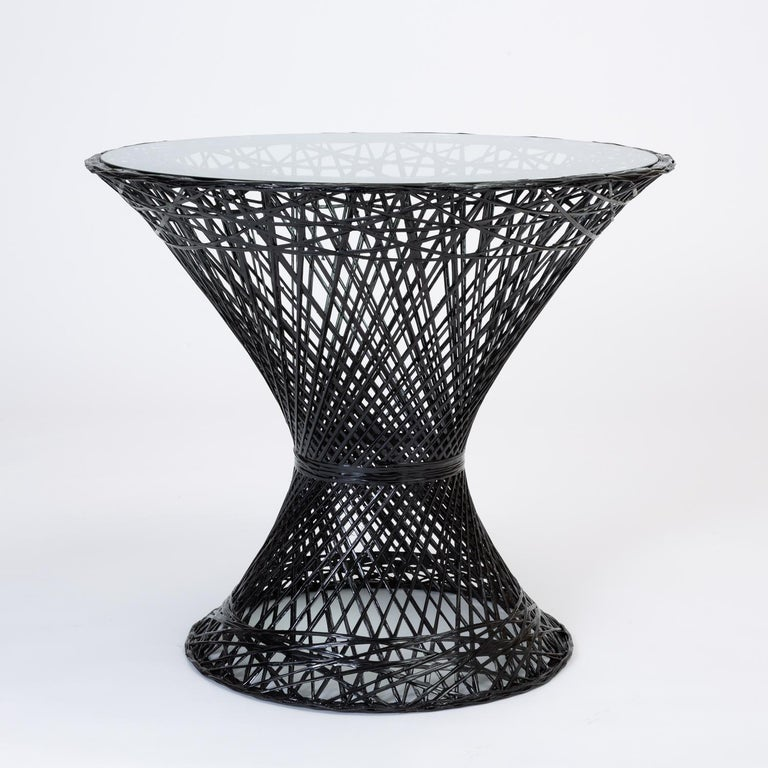 A bistro table by Russell Woodard for his family company's popular line of spun fiberglass patio furniture. The design features an hourglass shape and round pedestal base. The frame is described by an intricate lattice of fiberglass spokes with a