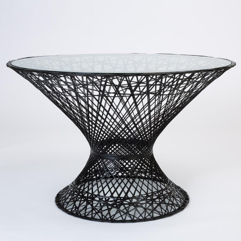 A dining table by Russell Woodard for his family company's popular line of spun fiberglass patio furniture. The design features an hourglass shape and round pedestal base. The frame is described by an intricate lattice of fiberglass spokes with a