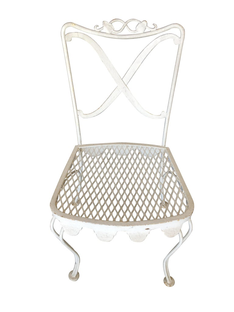 Woodard wrought iron scrolling pattern patio/outdoor set featuring four side chairs, two armchairs, and one glass top dining table. This set is currently repainted in white but can be changed to your color of choice, included in the
