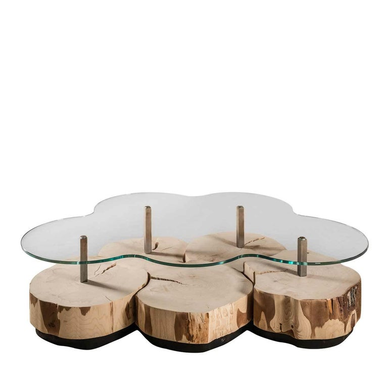 This sophisticated coffee table boasts a tempered glass top whose sinuous silhouette is mirrored by the stunning base composed of slices of a Swiss pine trunk fixed on a base of black laminated fir with LED strips that illuminate. Four polished iron